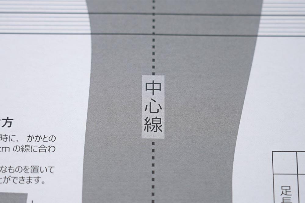 足長の測定シートの中心線に足の中心を合わせる